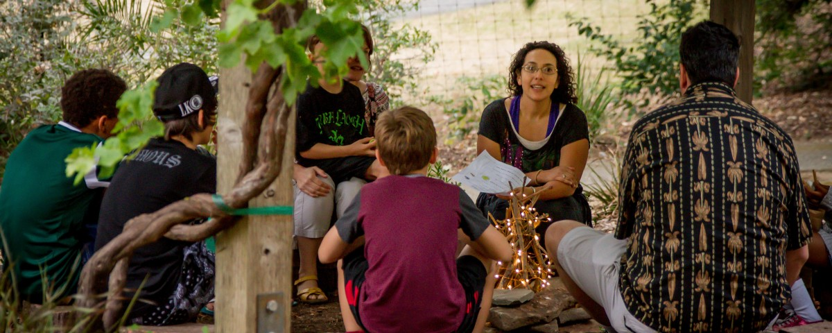 """Storytelling by the """"campfire"""" at our summer S'mores at Sundown event."""