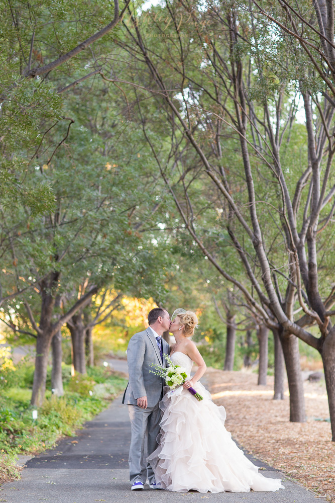 Bride and groom kiss under the ash trees at The Gardens on their wedding day.